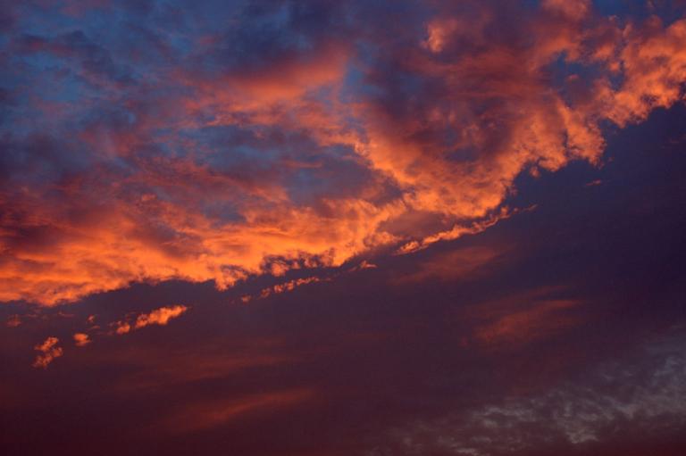 地表に斜めに侵入する日没直前の太陽の光の影響を強く受けた雲の写真